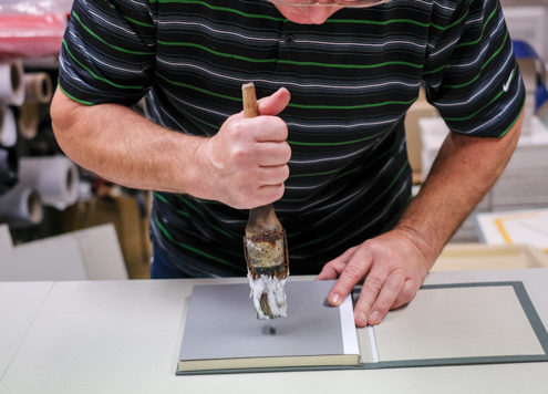 Man gluing cover to page block in bookbinding shop