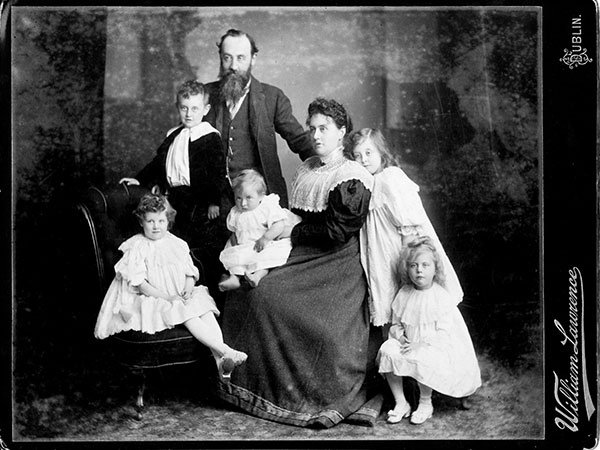 Family portrait from 1893 studio portrait of the Plunketts. Bearded father, formally dressed mother and 5 young children seated in a photo studio, looking serious.