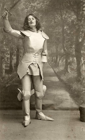 Old sepia-toned photograph of a woman in a stage setting, dressed in armour and gesticulating. (family)