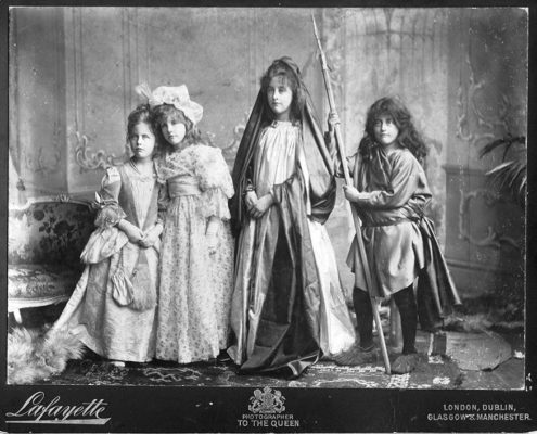 Old black and white studio family portrait of four young children in fancy dress, looking serious.