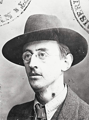 Studio portrait of young man with wire glasses and wide-brimmed hat. Family.