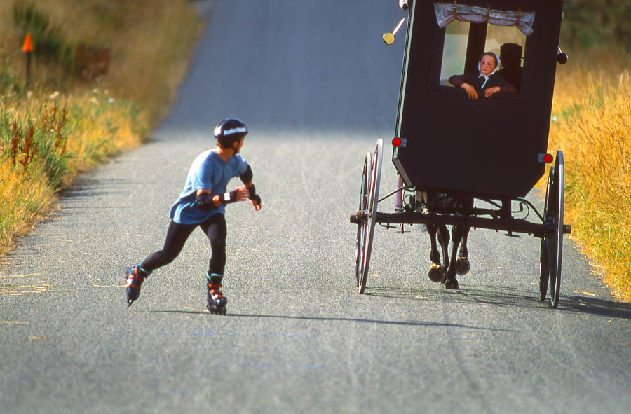 Amish buggy and rollerblader speeding past on lonely road